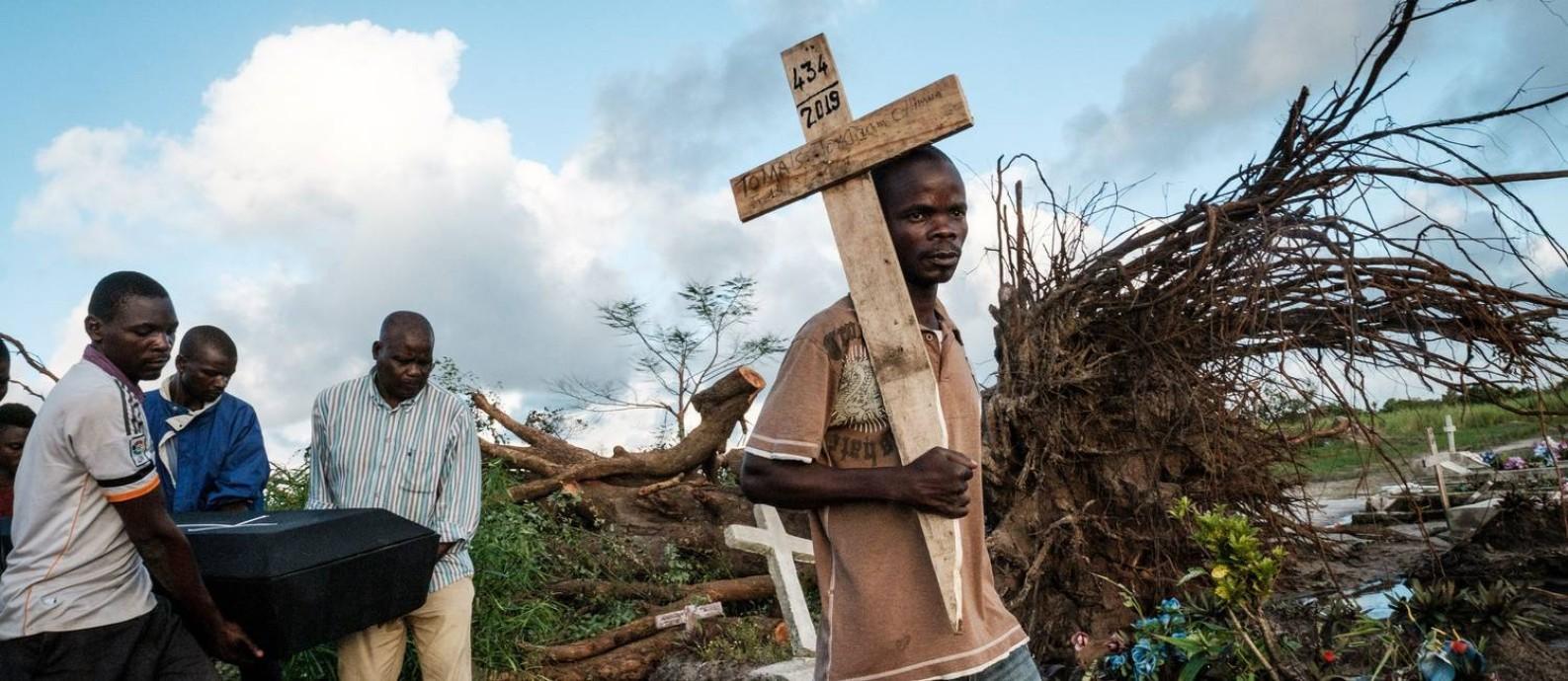 Pessoas levam corpos para serem enterrados em Beira, Moçambique, após passagem do ciclone Foto: YASUYOSHI CHIBA / AFP