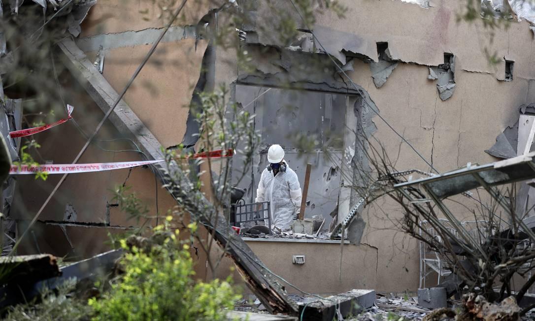 Um policial inspeciona a casa que foi atingida por um foguete ao norte de Tel Aviv, em Israel. Pelo menos sete pessoas ficaram feridas Foto: AMMAR AWAD / REUTERS