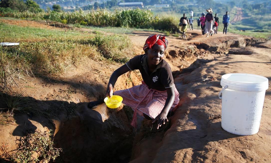 Mulheres buscam água em um riacho após o ciclone arrasar a região de Moçambique e do Zimbábue Foto: PHILIMON BULAWAYO / REUTERS