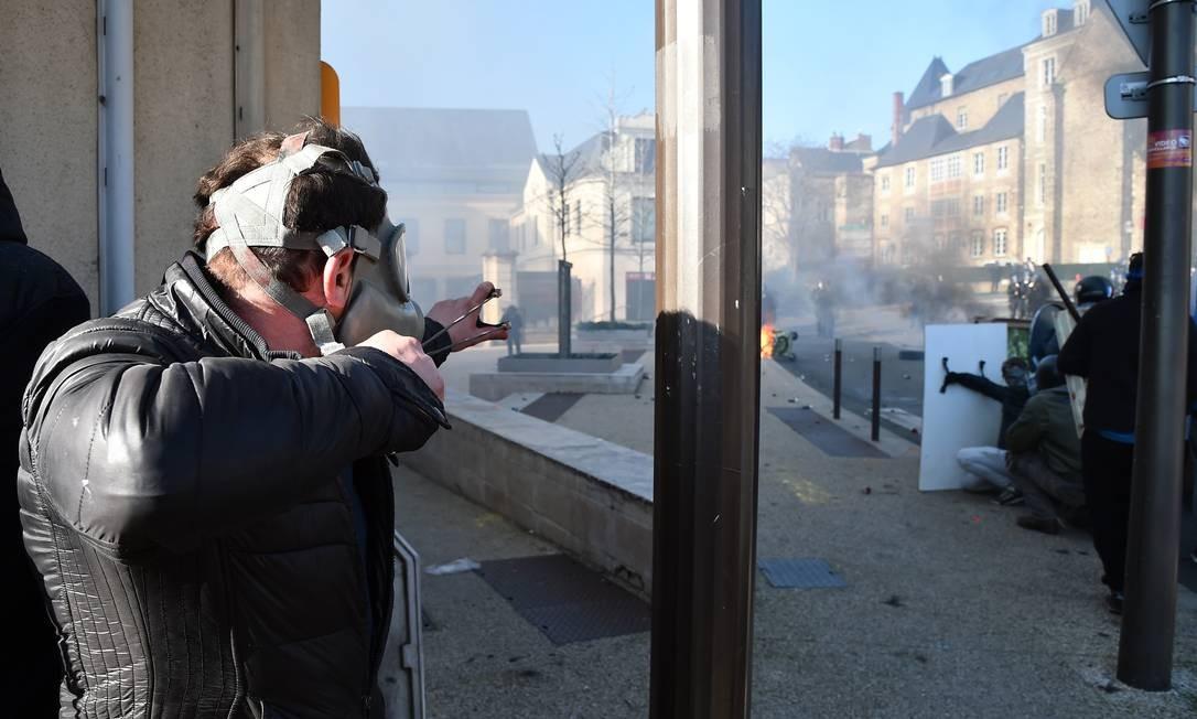 Usando atiradeira, um feirante agride policiais que tentam proteger o acesso à prefeitura. Os feirantes exigem o retorno do parque de diversões ao centro da cidade de Le Mans, na França Foto: JEAN-FRANCOIS MONIER / AFP