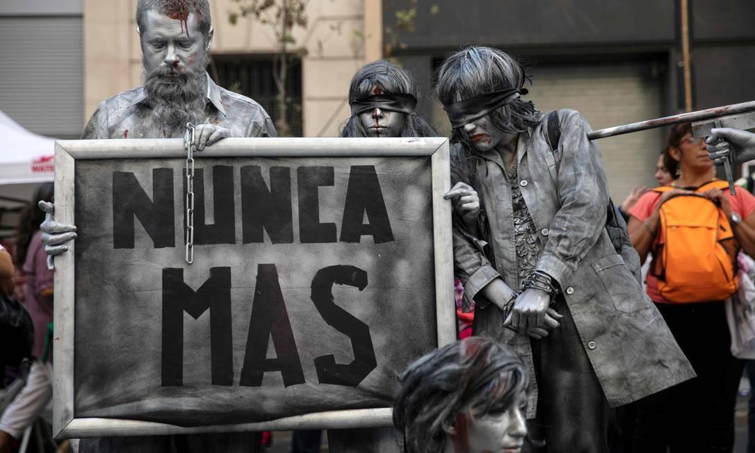"""Manifestantes fazem performance segurando uma placa com a inscrição """"Nunca Mais"""" durante um encontro para marcar o 43º aniversário do golpe militar de 1976, em Buenos Aires. Cerca de 30 mil pessoas desapareceram após serem presas durante a direita militar que governou a Argentina de 1976 a 1983, segundo organizações de direitos humanos Foto: EMILIANO LASALVIA / AFP"""