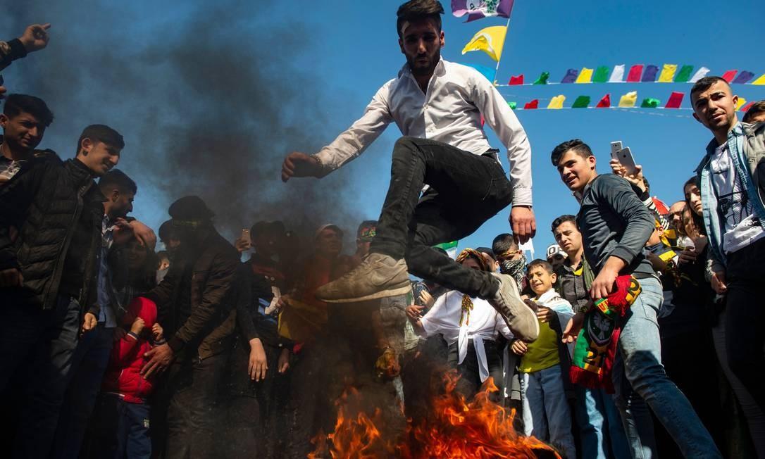 Um homem pula por cima do fogo enquanto milhares de partidários do principal Partido Democrático do Povo pró-Curdo (HDP) da Turquia se reúnem para celebrar o Ano Novo Curdo durante uma campanha para eleições locais em Istambul Foto: YASIN AKGUL / AFP