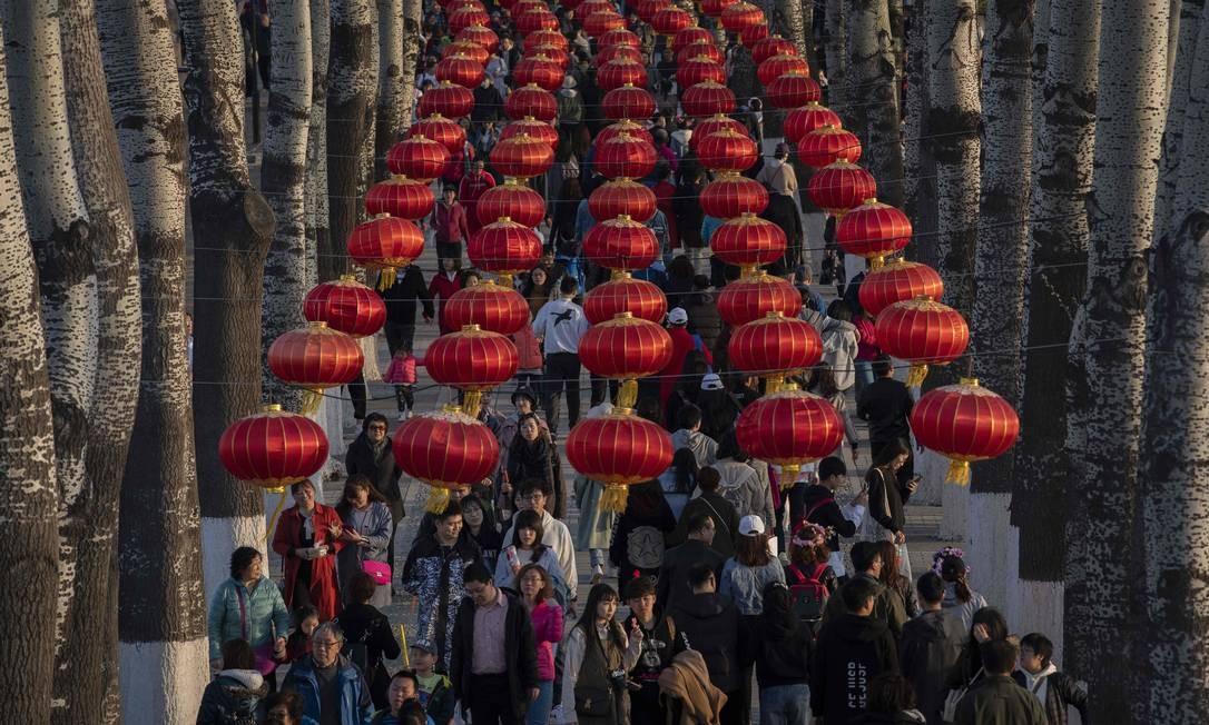 Pessoas andam sob lanternas no parque Yuyuantan, em Pequim Foto: NICOLAS ASFOURI / AFP