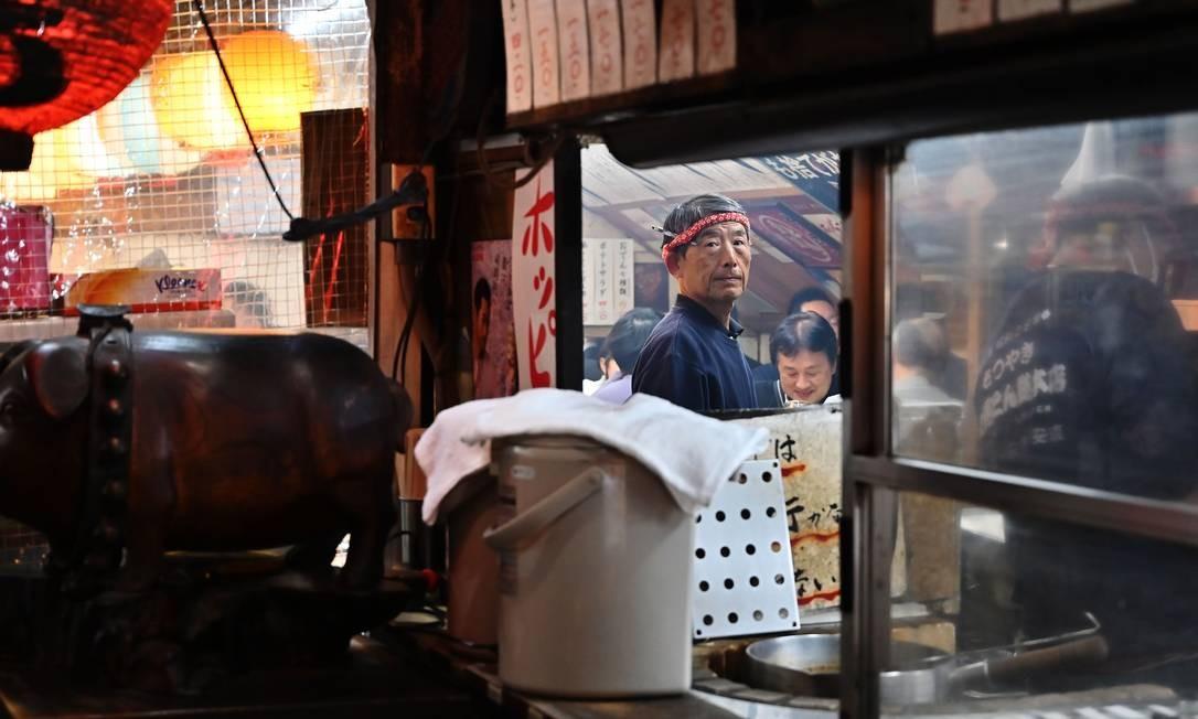 Um garçom é retratado enquanto trabalha em um restaurante num distrito de Tóquio Foto: CHARLY TRIBALLEAU / AFP
