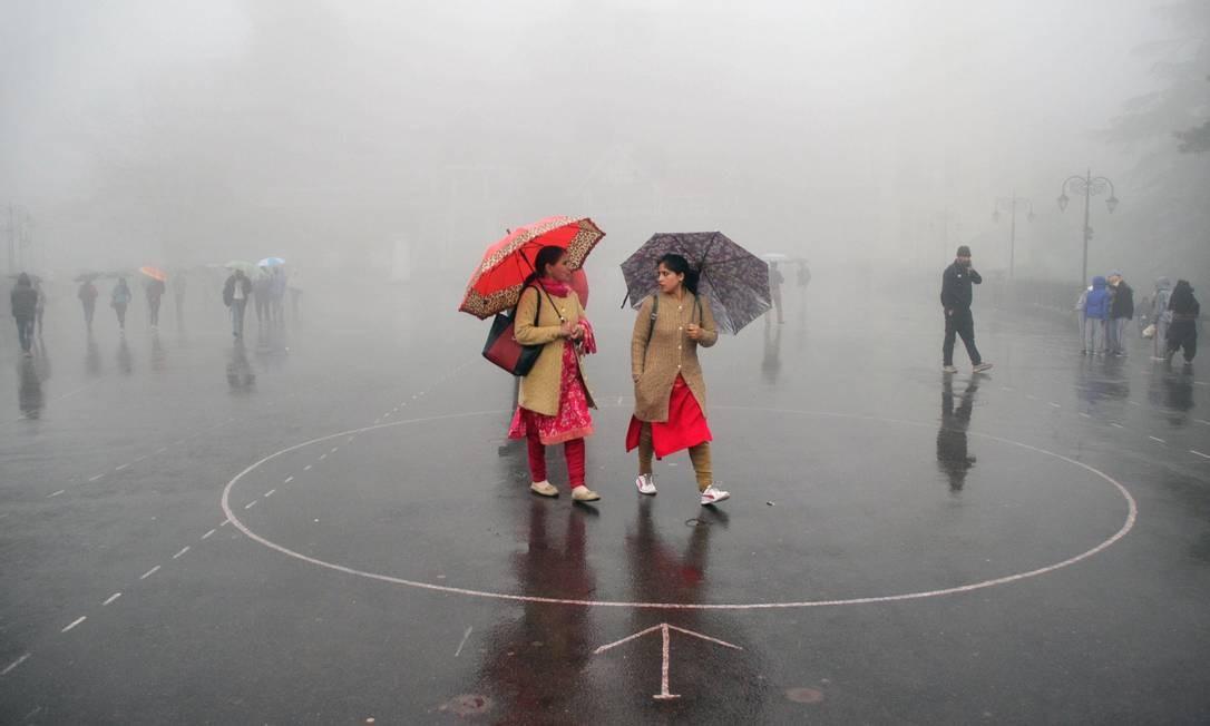 Mulheres indianas se protegem da chuva enquanto caminham na cidade montanhosa de Shimla, no norte da Índia Foto: STR / AFP