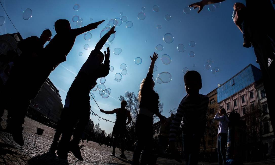 Crianças brincam de estourar bolhas de sabão feitas pelo cantor polonês Martin, em frente ao Teatro Nacional Eslovaco, em Bratislava, Eslováquia Foto: JOE KLAMAR / AFP
