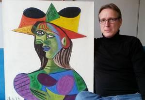 O detetive de arte Arthur Brand posa com o quadro de Picasso recuperado Foto: STRINGER / AFP