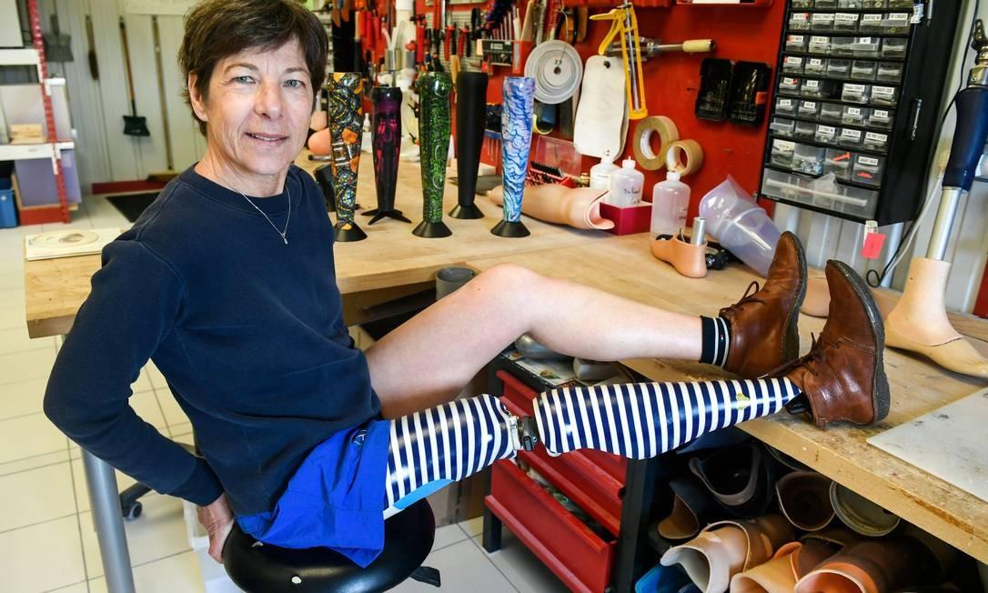 """Evelyne Briand posa com sua prótese customizada na ALGO, empresa especializada em próteses, em Brest, oeste da França. """"Não aguentei a primeira prótese, com espuma e meia. Estava desatualizada"""", diz Briand, mostrando com orgulho a perna direita decorada com listras azuis e brancas Foto: FRED TANNEAU / AFP"""