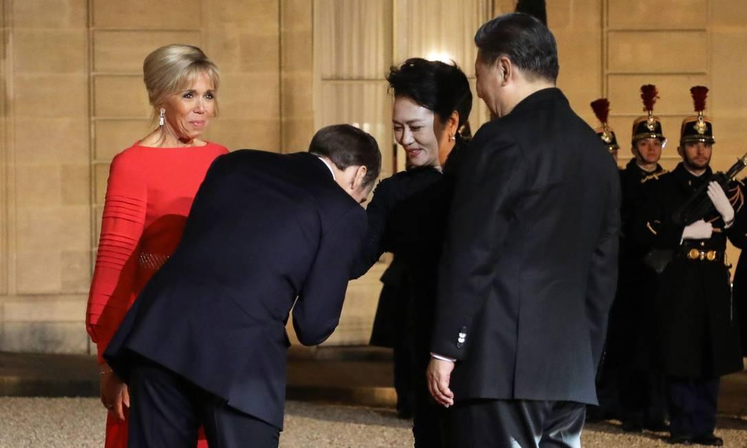 Ao lado de sua esposa, Brigitte Macron, o presidente da França, Emmanuel Macron, beija a mão da primeira-dama da China, Peng Liyuan, antes de um jantar oferecido ao presidente chinês, Xi Jinping, no Palácio do Eliseu, em Paris. Xi Jinping está em uma visita oficial de três dias à França, onde deverá assinar uma série de acordos bilaterais e econômicos sobre energia, indústria alimentícia, transporte e outros setores Foto: LUDOVIC MARIN / AFP