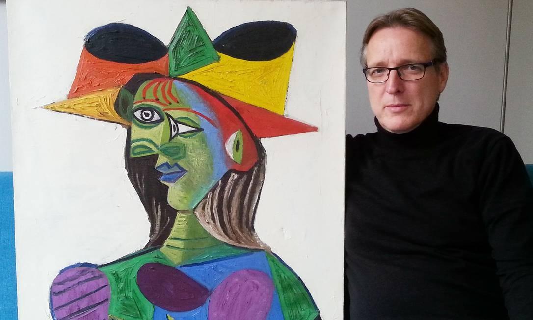 """O detetive holandês Arthur Brand, conhecido como """"Indiana Jones da arte"""", posa em sua casa, em Amsterdã, ao lado da pintura de Picasso """"Buste de femme (Dora Maar)"""", roubada de um iate saudita, na Riviera Francesa, em 1999. Brand voltou a mostrar seu talento ao recuperar o quadro, avaliado em 25 milhões de euros. A descoberta do raro retrato de Maar, uma das mais influentes amantes de Pablo Picasso, culmina uma investigação de quatro anos sobre o roubo no iate de luxo Coral Island, enquanto estava ancorado em Antibes Foto: STRINGER / AFP"""