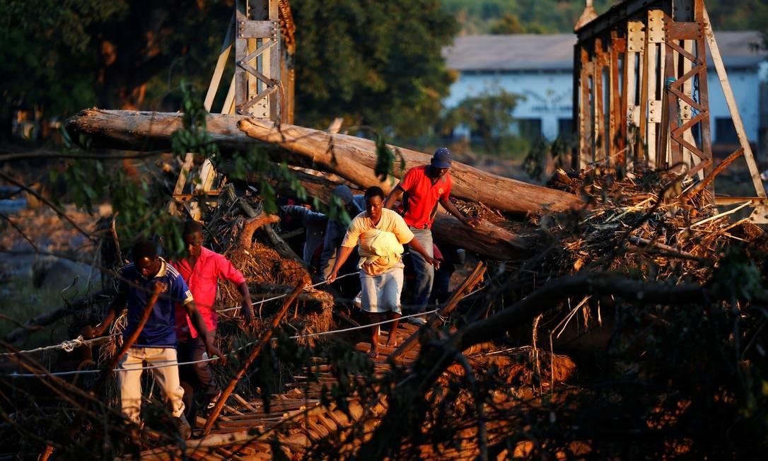 Sobreviventes do ciclone Idai atravessam uma ponte temporária quando chegam ao centro de negócios de Coppa para receber ajuda em Chipinge, no Zimbábue Foto: PHILIMON BULAWAYO / REUTERS