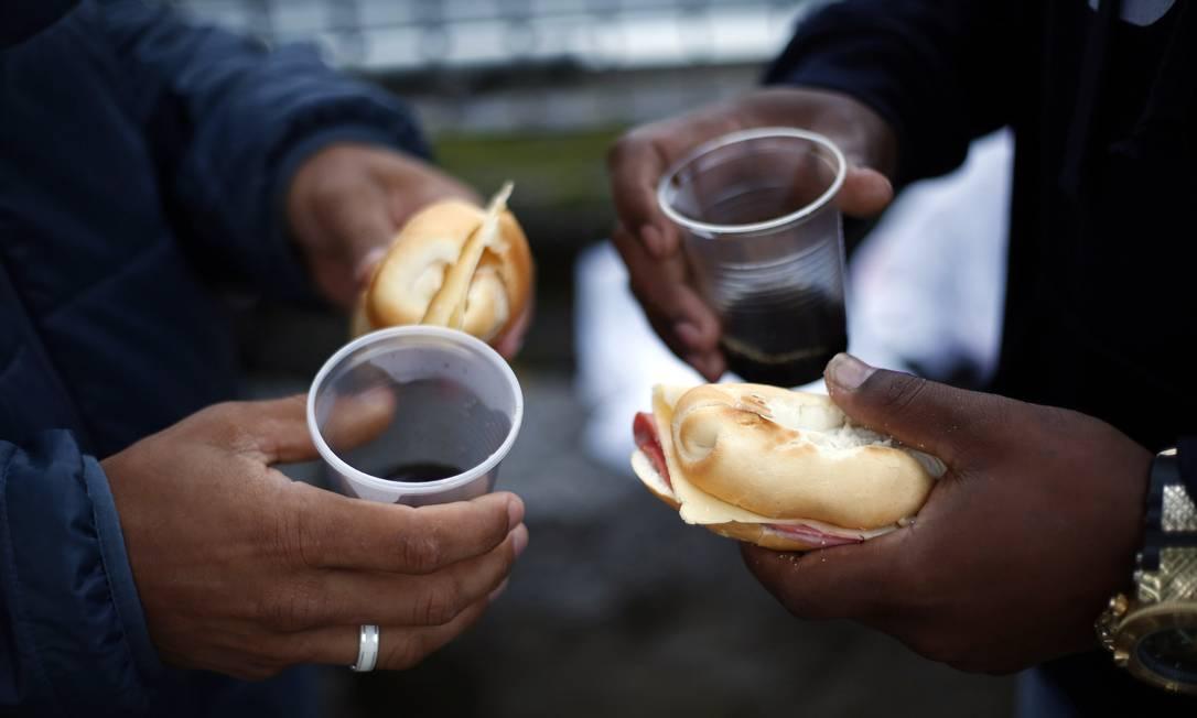 Na fila para tentar um novo trabalho, desempregados compartilham o café da manhã Foto: Marcos de Paula / Agência O Globo