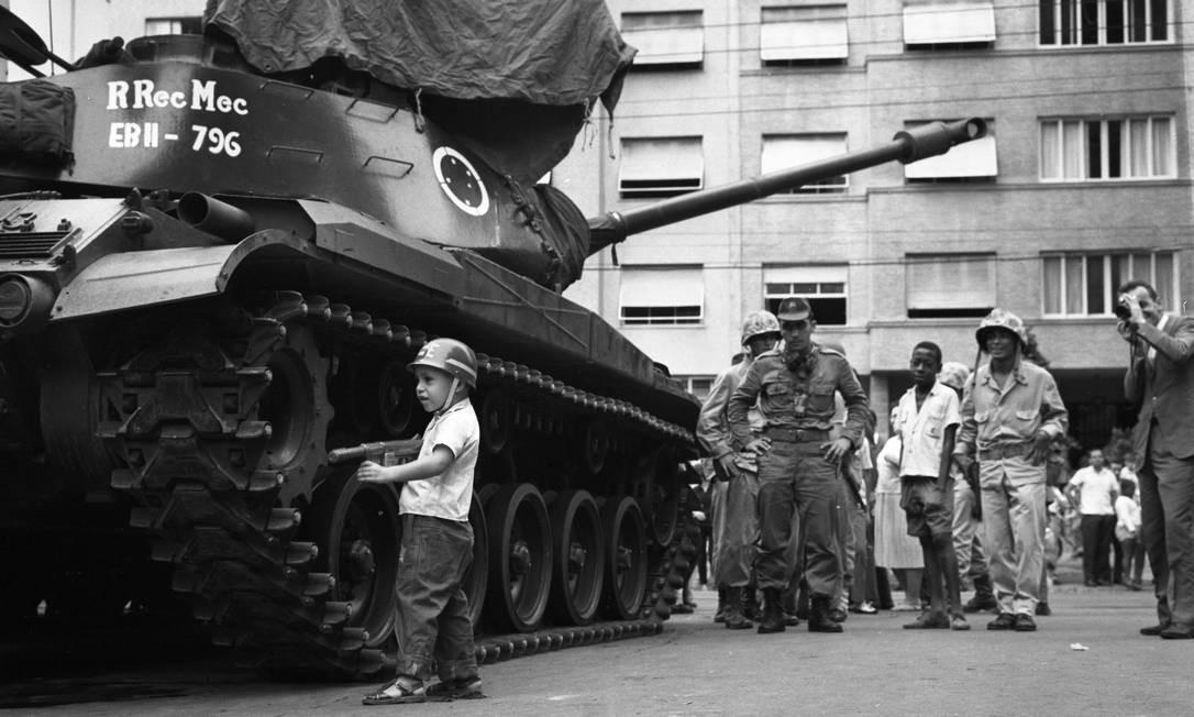 Uma criança usando capacete e portando uma arma de brinquedo é observada por soldados e civis enquanto brinca ao lado de um tanque do Exército Foto: Agência O Globo