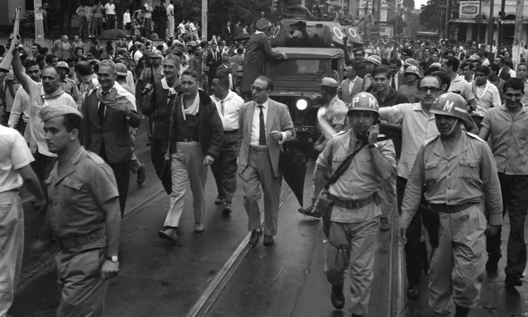 O radialista e então deputado estadual Raul Brunini (guarda chuva) caminha ao lado de militares nas ruas do Rio Foto: Agência O Globo