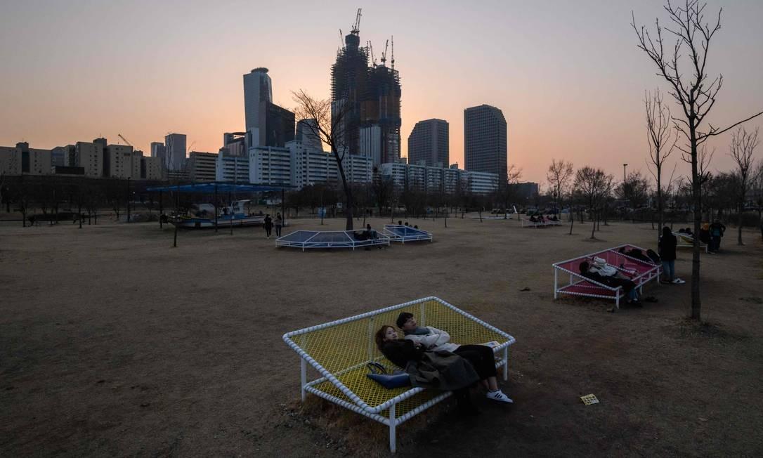 Um casal senta em um banco no parque Yeouido, em Seul, na Coreia do Sul. Dados do governo apontam que o número de casamentos na no país caiu para seu nível mais baixo em mais de 40 anos em 2018, com 257.622 casais formalizando a união em comparação com 264.455, em 2017 Foto: ED JONES / AFP