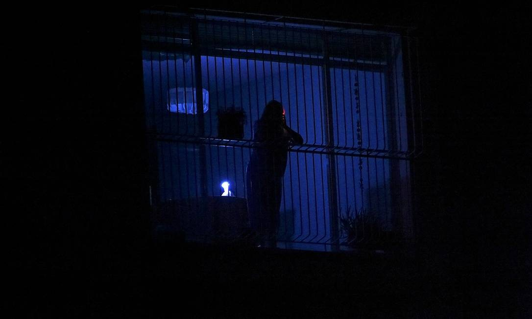 Uma pessoa olha pela janela durante uma queda de energia em Caracas. Novo apagão atingiu muitas regiões da Venezuela, incluindo grande parte de Caracas. O corte de energia na capital ocorreu às 13h28 (horário de Brasília) e derrubou a eletricidade no centro da cidade. Sinais de celular também foram interrompidos Foto: JUAN BARRETO / AFP