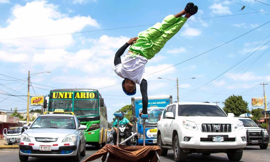 Um artista de rua se apresenta em meio ao tráfego intenso em Manágua, na Nicarágua Foto: MAYNOR VALENZUELA / AFP