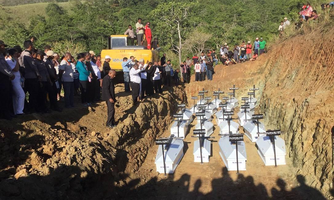 Caixões contendo os restos mortais de vítimas da inundação que não foram identificadas são enterrados em uma cova coletiva em Papua, na Indonésia Foto: NETHY DHARMA SOMBA / AFP