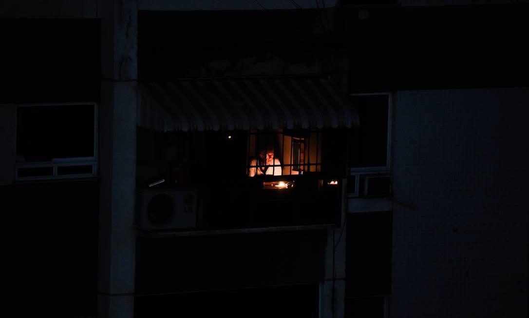 Sem energia elétrica, um homem olha pela janela durante uma queda de energia em Caracas na Venezuela Foto: FEDERICO PARRA / AFP