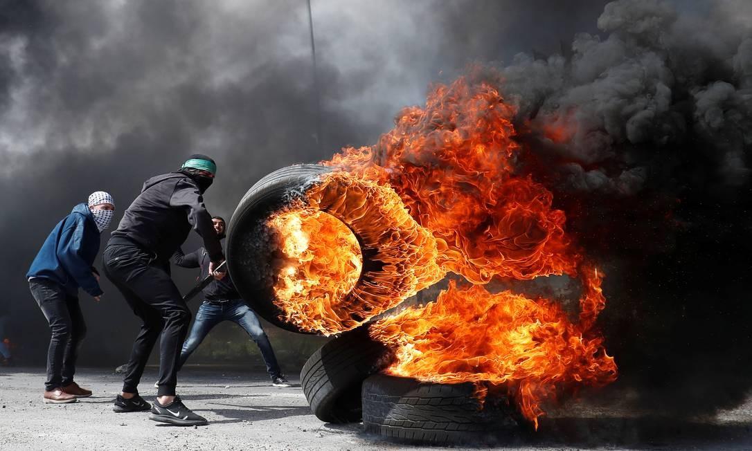 Manifestante palestino incendeia pneus durante confrontos com tropas israelenses perto do assentamento judaico de Beit El, na região da Cisjordânia ocupada por Israel Foto: MOHAMAD TOROKMAN / REUTERS
