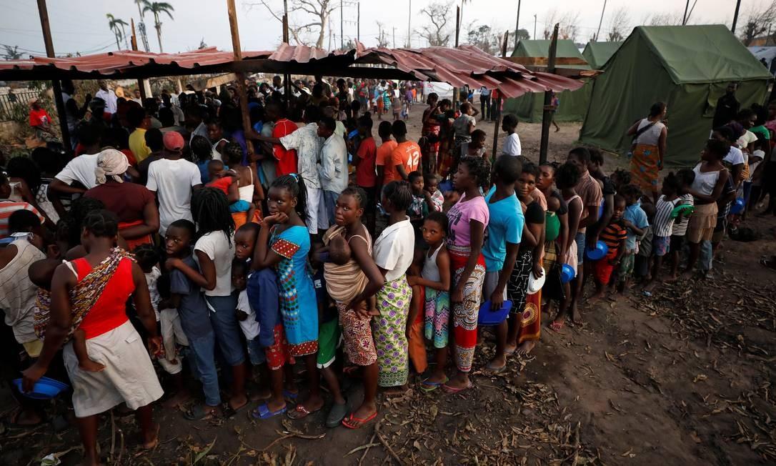 Moçambicanos fazem fila para retirar comida em um acampamento para desabrigados do ciclone Idai que arrasou Moçambique. Mais de 2 milhões foram afetados Foto: MIKE HUTCHINGS / REUTERS