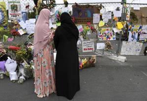 Duas muçulmanas observam as homenagens às vítimas dos ataques a duas mesquitas em Christchurch, na Nova Zelândia Foto: WILLIAM WEST / AFP/23-3-2019