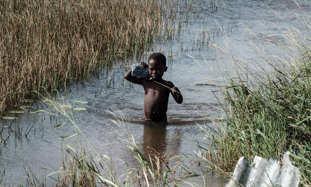 Criança passa por área inundada pelo ciclone Idai, em Beira, Moçambique Foto: YASUYOSHI CHIBA / AFP