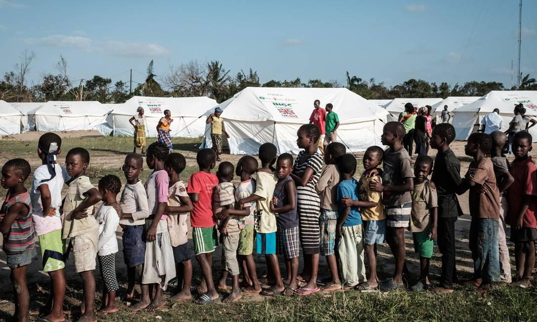 Ciclone Idai atingiu Moçambique no dia 15 de março e deixou rastro de destruição. Na foto, crianças em fila de distribuição de alimentos Foto: YASUYOSHI CHIBA / AFP