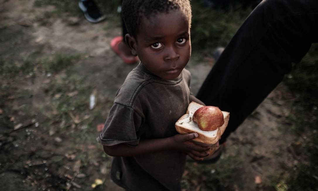 Criança caminha depois de receber alimento distrubuído por mercado local em centro de evacuação em Dondo, Moçambique Foto: YASUYOSHI CHIBA / AFP