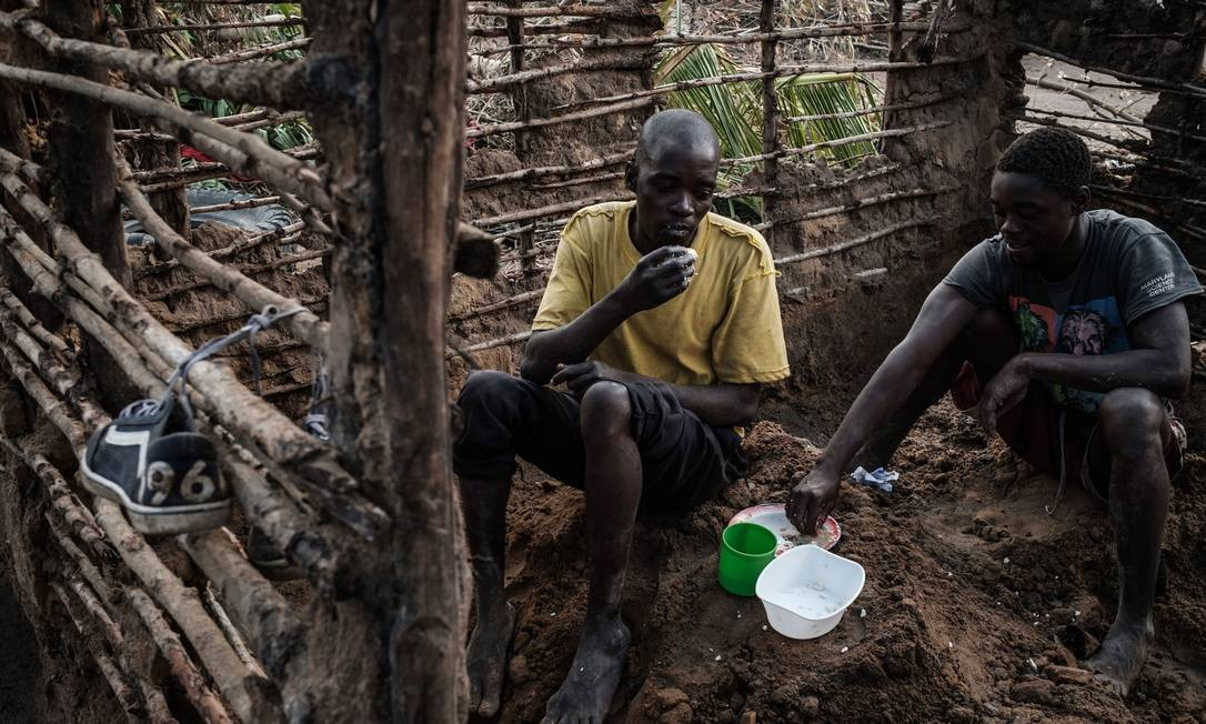 Homens almoçam enquanto consertam casa que foi destruída pelo ciclone Idai em Beira Foto: YASUYOSHI CHIBA / AFP