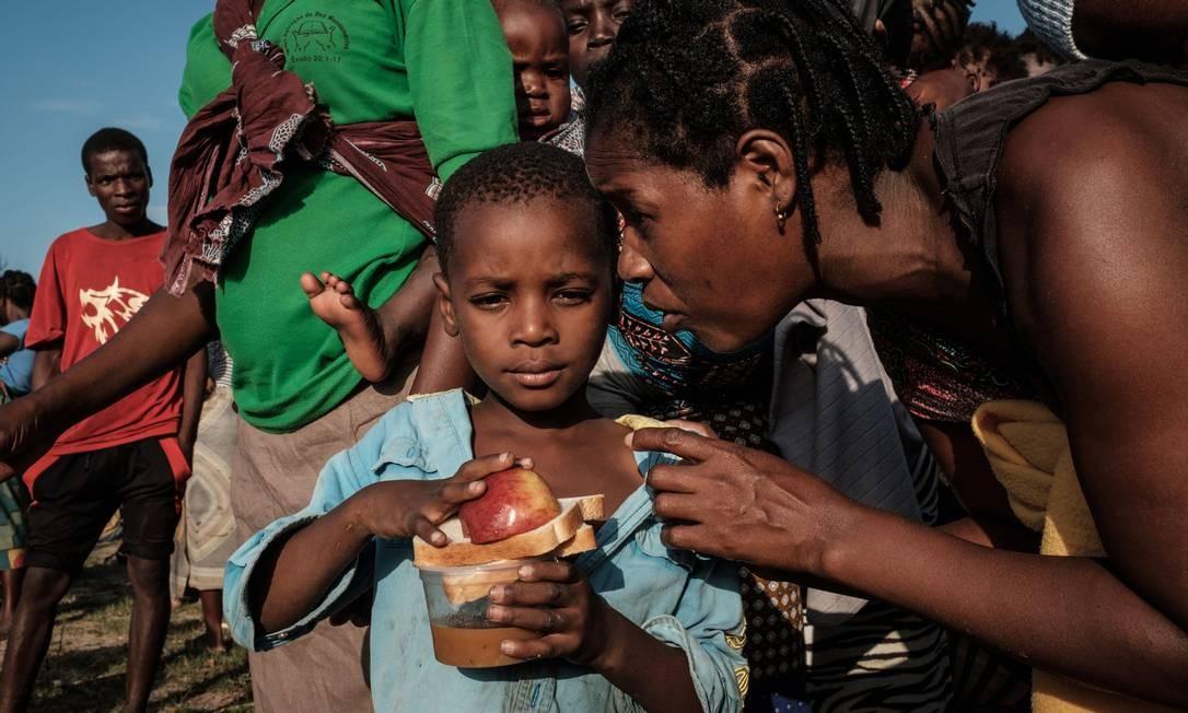 Uma criança escuta sua mãe após receber alimento em centro de evacuação em Dondo Foto: YASUYOSHI CHIBA / AFP