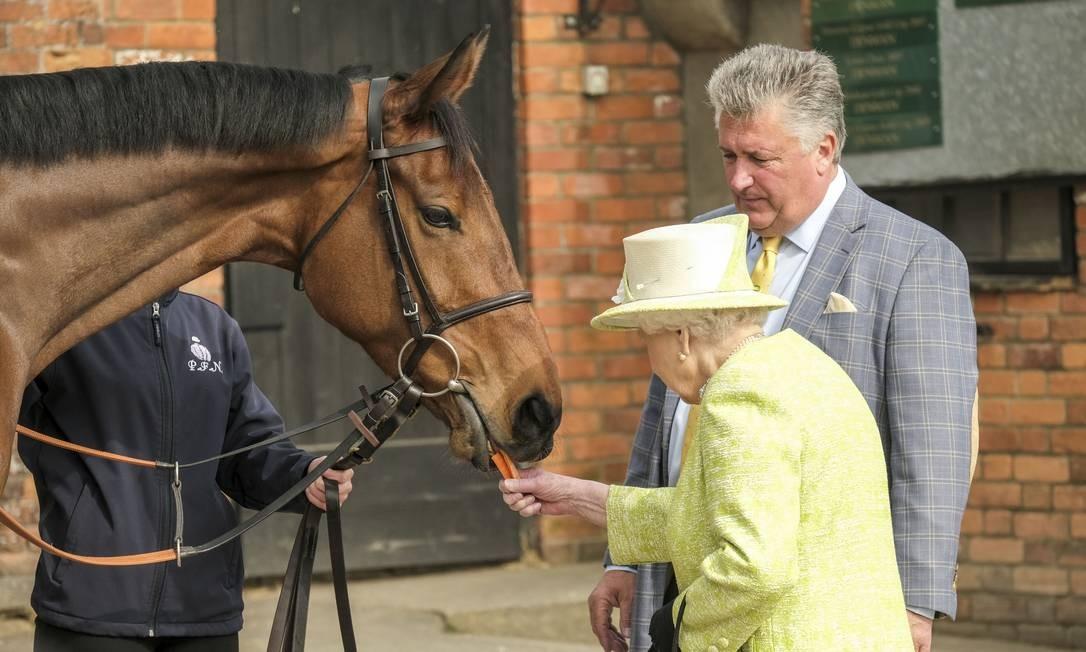 A rainha Elizabeth II, da Grã-Bretanha, alimenta com uma cenoura a um cavalo durante visita a um estábulo, em Ditcheat, Grã-Bretanha Foto: POOL / REUTERS