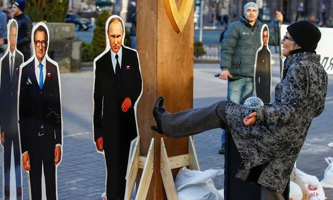 Uma mulher chuta uma figura representando o presidente russo, Vladimir Putin, em Kiev, Ucrânia Foto: VASILY FEDOSENKO / REUTERS
