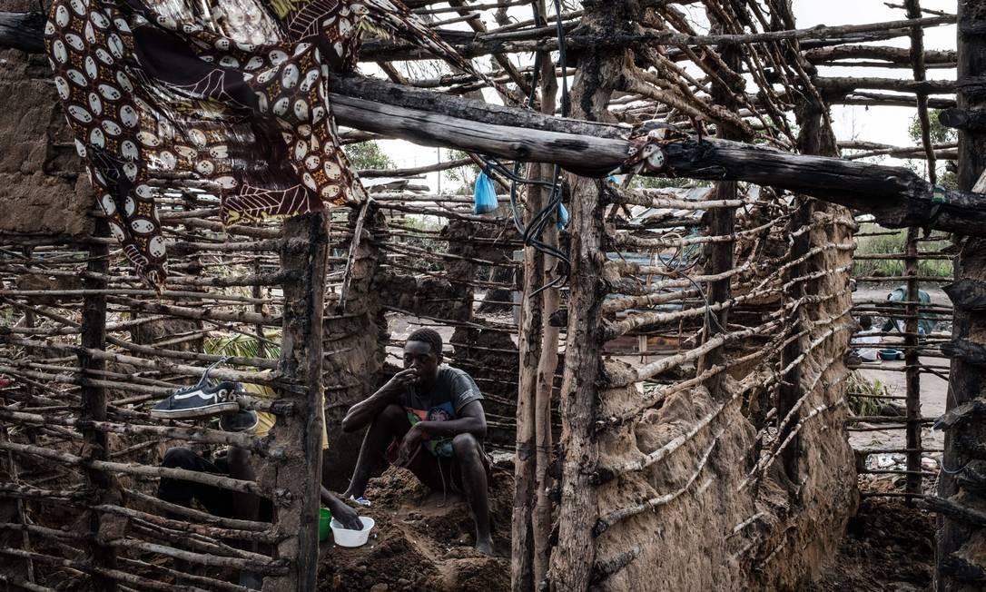Os homens almoçam enquanto consertam uma casa que foi destruída pelo vento do ciclone Idai, na cidade de Beira, Moçambique. Cinco casos de cólera foram confirmados em Moçambique após o ciclone que devastou o país, matando pelo menos 468 pessoas, em 15 de março Foto: YASUYOSHI CHIBA / AFP