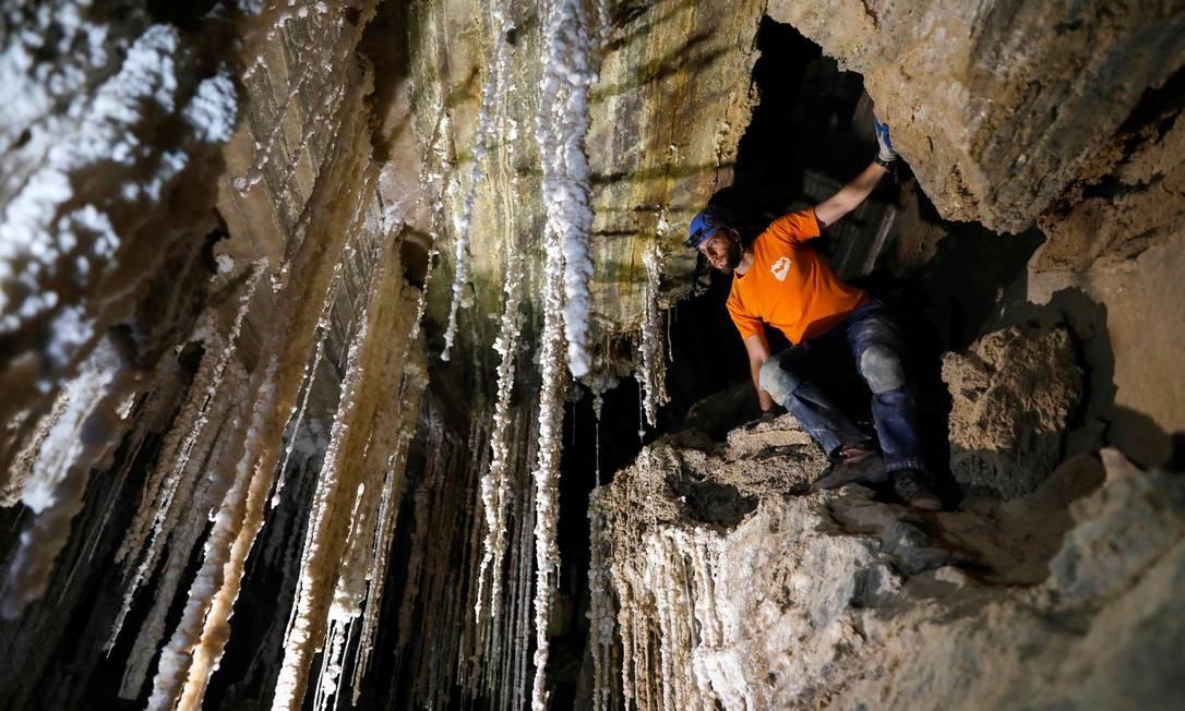 Explorador mostra a jornalistas estalactites salinas na caverna de Malham, no Monte Sodoma, localizada na parte sul do Mar Morto, em Israel Foto: MENAHEM KAHANA / AFP