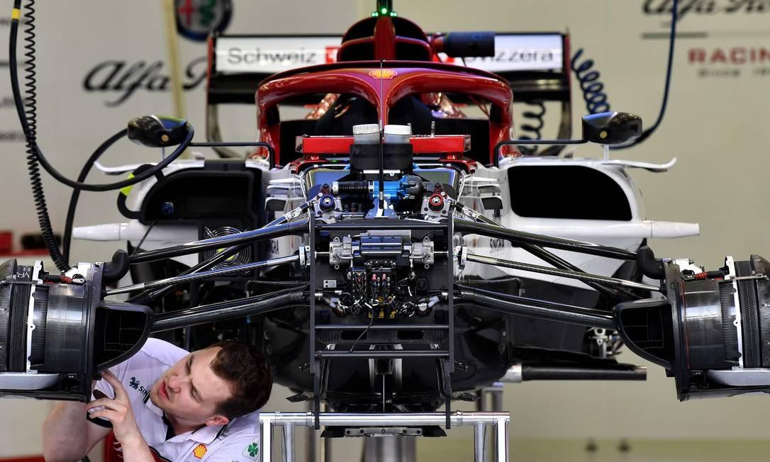 Um mecânico trabalha no carro do piloto italiano da Alfa Romeo Sauber, Antonio Giovinazzi, antes do Grande Prêmio de Fórmula 1 no circuito internacional de Barém Foto: ANDREJ ISAKOVIC / AFP