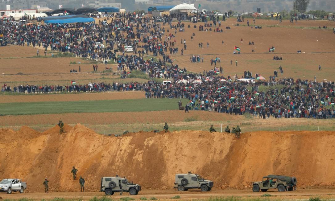 """Foto de 30 de março de 2018 mostra o kibbutz de Nahal Oz, na fronteira com a Faixa de Gaza, onde palestinos participam de um protesto na cidade, comemorando o Dia da Terra, com veículos militares israelenses vistos abaixo em primeiro plano. Um ano após o início dos protestos, rotulados como a """"Grande Marcha de Retorno"""", e os confrontos na fronteira entre Gaza e Israel, mais de 200 palestinos foram mortos por disparos israelenses. Mais de 8 mil cirurgias foram adiadas nos hospitais de Gaza, segundo a OMS Foto: JACK GUEZ / AFP"""