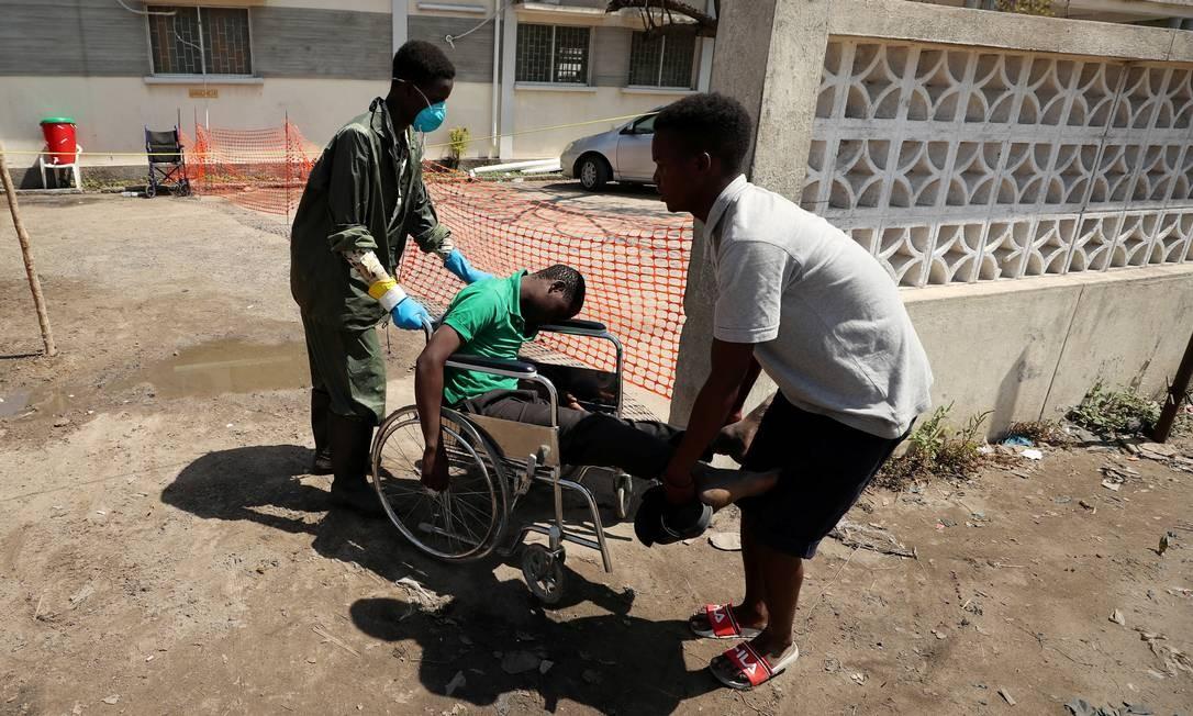 Um membro da equipe médica usa uma máscara protetora enquanto auxilia um homem que chega a um centro de tratamento de cólera criado após o ciclone Idai, na cidade de Beira, em Moçambique Foto: MIKE HUTCHINGS / REUTERS