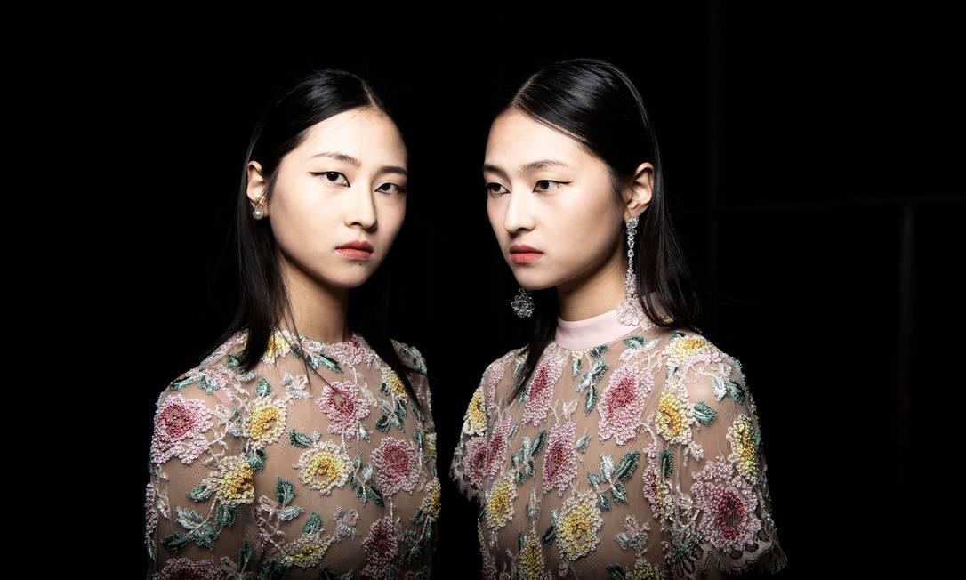 Duas modelos posam nos bastidores antes de apresentar a coleção do designer chinês Zhang Peng, durante a China Fashion Week, em Pequim Foto: FRED DUFOUR / AFP
