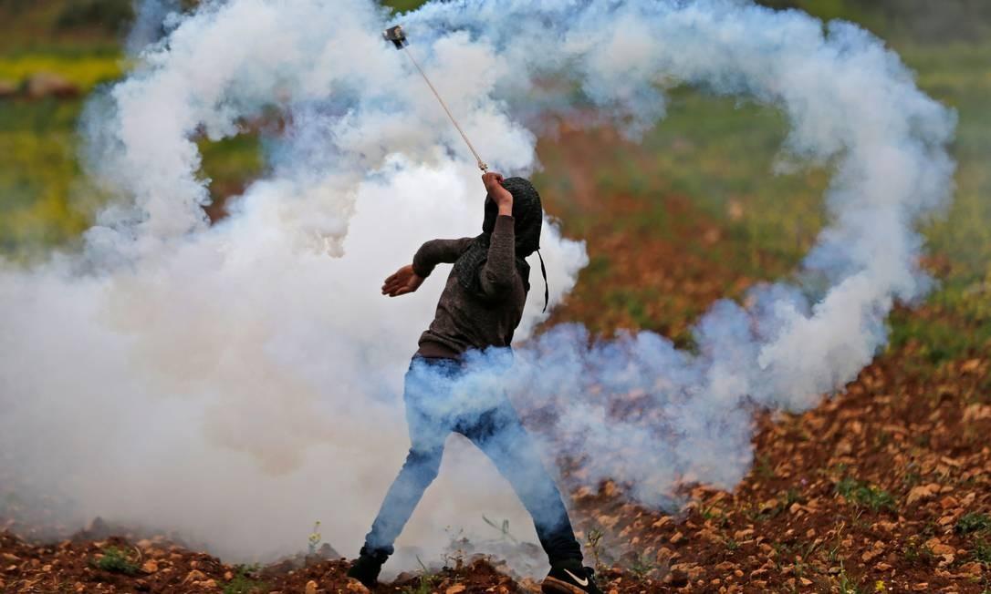 Um manifestante palestino usa um estilingue para lançar uma bomba de gás lacrimogêneo disparada por tropas israelenses durante os confrontos após uma manifestação na vila de Mughayir, na Cisjordânia ocupada por Israel Foto: ABBAS MOMANI / AFP