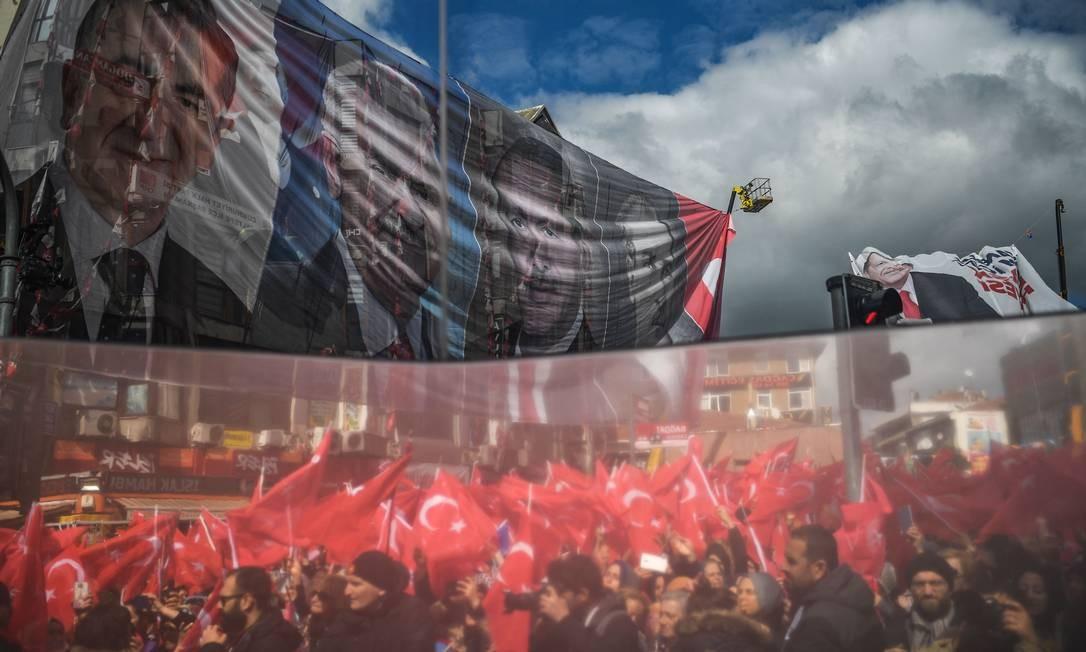 Lateral de ônibus reflete os partidários do Partido da Justiça e Desenvolvimento durante uma reunião eleitoral em Istambul. O presidente turco está fazendo campanha por votos para seu partido antes das eleições municipais de 31 de março Foto: OZAN KOSE / AFP