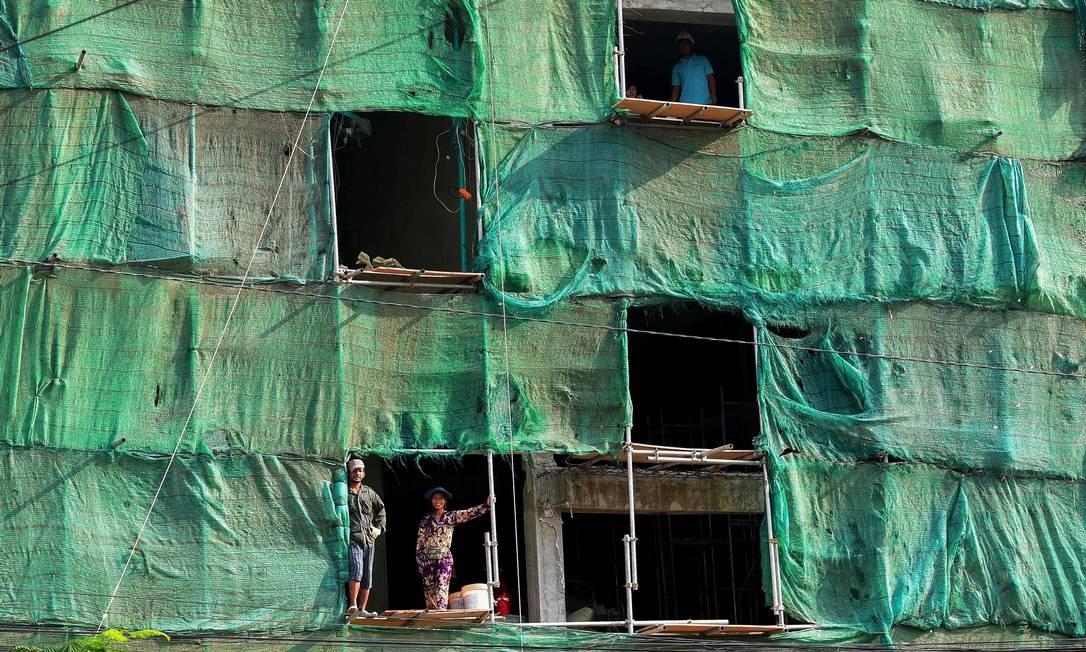 Trabalhadores do Camboja olham para fora da construção de um prédio em Phnom Penh Foto: TANG CHHIN SOTHY / AFP