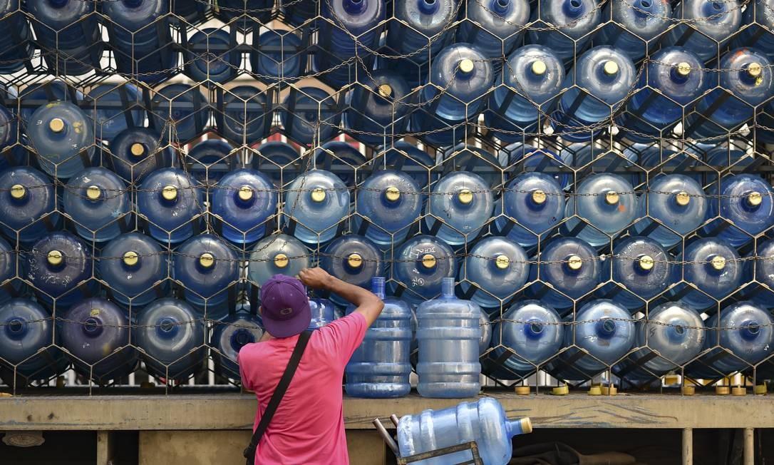 Um homem coloca galões vazios de volta em um caminhão de distribuição privada de água potável em Caracas, Venezuela Foto: YURI CORTEZ / AFP