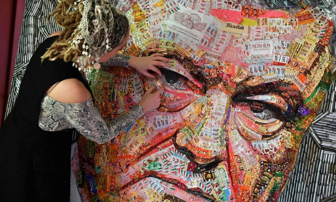 """A artista ucraniana Daria Marchenko cria uma obra de arte em grande escala intitulada """"O rosto da corrupção"""" representando o presidente Petro Poroshenko feito com embalagens doces da Roshen, empresa de doces de Poroshenko, em sua oficina, em Kiev, dias antes das eleições presidenciais, em 31 de março Foto: SERGEI SUPINSKY / AFP"""