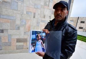 O franco-marroquino Mustafá Tarbouni segura o dossier com documentos e fotos da sobrinha Jana, que hoje estaria com 7 anos, que tenta encontrar na Síria Foto: GIUSEPPE CACACE/AFP