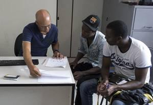 Haitiano Hugo Alindo (centro) leva o amigo Moise Pierre-Rene, recém-chegado do Chile, para regularizar situação em serviço da prefeitura Foto: Edilson Dantas 28-03-2019 / Agência O Globo