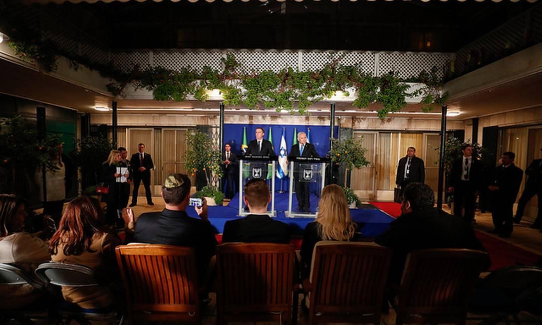 Bolsonaro e Netanyahu fazem pronunciamento na residência oficial do premier; ambos são filmados pelo senador Flávio Bolsonaro, que usa um quipá (solidéu judaico) em estampa camuflada e com as iniciais em hebraico do Exército israelense Foto: Divulgação/Palácio do Planalto