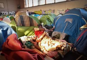 Homem acorda em tenda de ginásio ocupado por cerca de 250 migrantes na França Foto: LOIC VENANCE / AFP