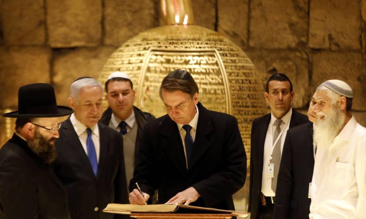 Jair Bolsonaro, acompanhado pelo primeiro-ministro israelense, Benjamin Netanyahu, assina livro durante sua visita a uma sinagoga nos túneis do Muro das Lamentações, na Cidade Velha de Jerusalém, nesta segunda-feira (1), segundo dia da visita oficial do presidente brasileiro a Israel Foto: POOL / REUTERS