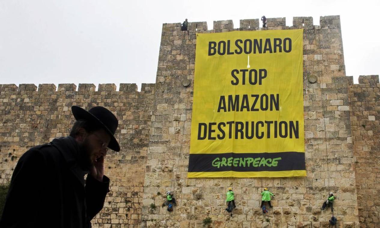 """Ativistas do Greenpeace penduram uma faixa nas muralhas da Cidade Velha de Jerusalém com mensagem destinada ao presidente brasileiro: """"Bolsonaro, pare a destruição da Amazônia"""", diz a mensagem Foto: OHAD ZWWINGENBERG / AFP"""